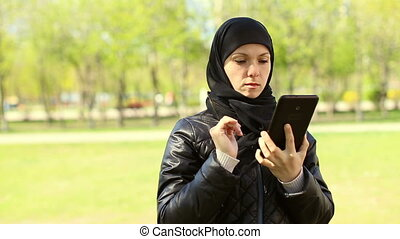 Muslim woman with a tablet in her hands outdoors. - Girl...