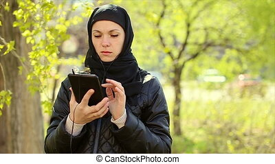 Muslim woman with a tablet in her hands outdoors.Full hd video