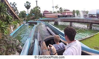 family have fun sliding down in kanoe in Aquapark