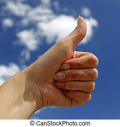 hand showing OK sign with blue sky in the background