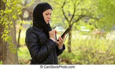 Muslim woman with a tablet in her hands outdoors.Full hd...