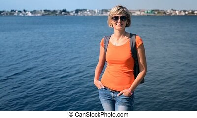 Casual woman with backpack standing against sea with hair...