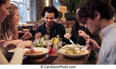 happy friends eating and drinking at restaurant - leisure,...