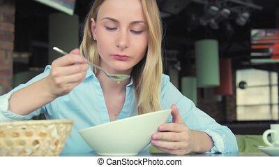 Attractive woman eating tasty soup in cafe in the city.