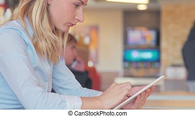 Working at the cafe. Young beautiful long hair woman sitting at the table and using tablet.