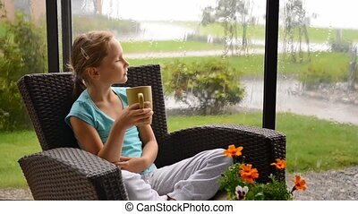 Rainy summer day. Calm little child girl sitting in armchair...