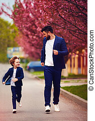 happy father and son in suits running along the spring...