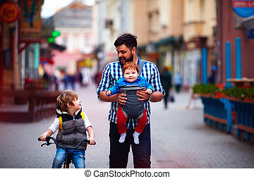 happy father and two sons on the city walk. Parental leave....