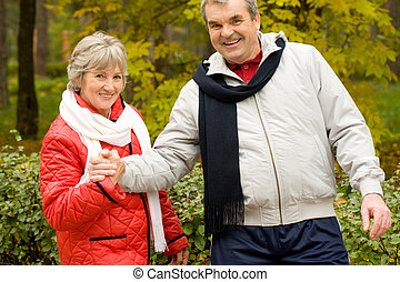 In autumnal park - Photo of two aged people looking at...