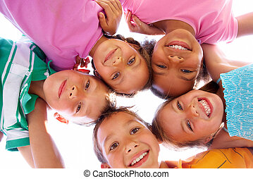 Happy time - Below view of happy children embracing each...