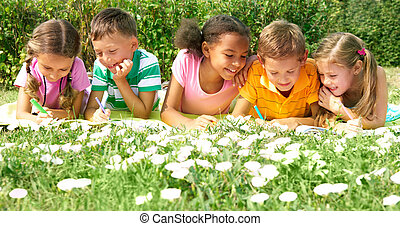 Spending time outdoors - Portrait of cute kids drawing in...