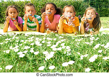 Bubble play - Portrait of cute friends having bubble fun on...