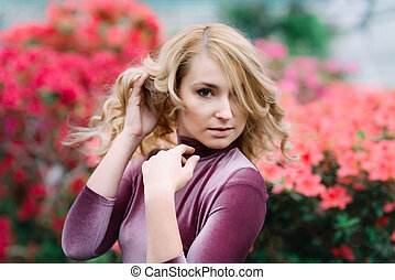 Young pretty woman between red flowers - Young pretty blonde...