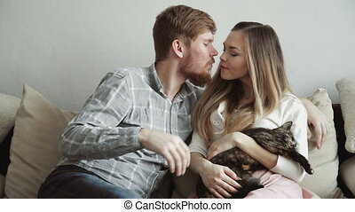 Couple is sitting on the couch sofa at home stroking a cat,...
