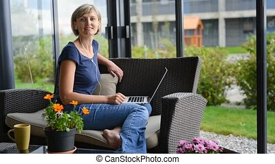 Woman with laptop - Young woman sitting on the terrace with...