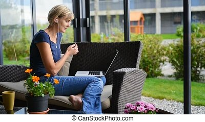 Woman having video chat - Young woman sitting on the terrace...