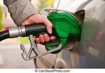 Refilling The Car - male hand refilling the car with fuel on...
