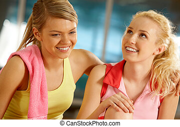 Gilrs in gym - Portrait of two pretty girls during workout...
