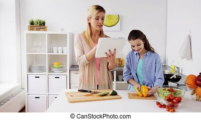 family cooking dinner using tablet pc at kitchen - food,...