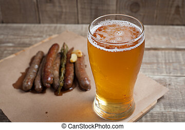 Fried sausages and mug of cold beer on a wooden table. Top view