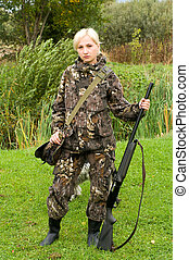 Girl hunter - Blond girl in camouflage with a shotgun