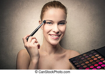 Woman doing her makeup - Young woman doing her makeup