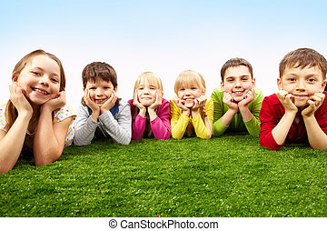 Resting children - Image of happy boys and girls lying on a...