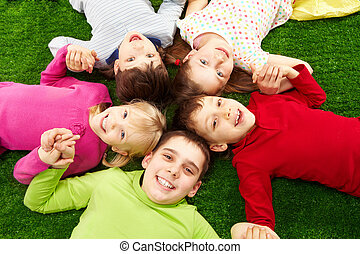 Happy children - Image of smiling young boys and girls lying...