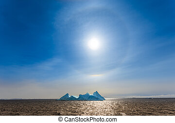Sun Halo shining over the blue iceberg and ocean, North...
