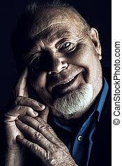 positive old man - Portrait of a smiling old man over black...