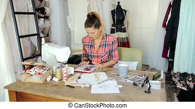 Female with tablet in parlour - Female dressmaker in casual...