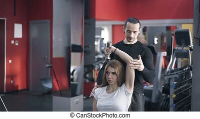 Trainer helping woman to do a dumbbell exercise, tilt down -...