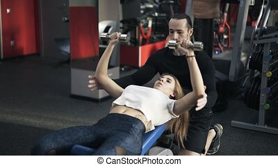 Trainer helping woman to do a dumbbell exercise on bench