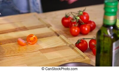 Chef cuts cherry tomatoes close-up.