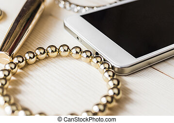 Mascara, mobile phone and gold bracelet