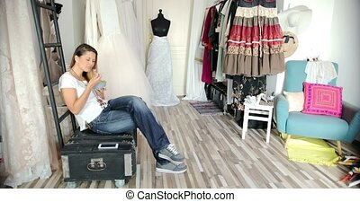 Female tailor eating in parlour - Young female in casual...