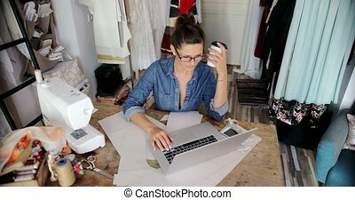 Female with laptop and coffee in parlour - Young woman in...