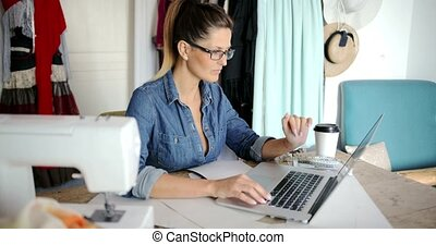 Pensive female with laptop working - Young casual woman in...