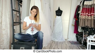 Woman in tailor's shop with phone - Young female in casual...