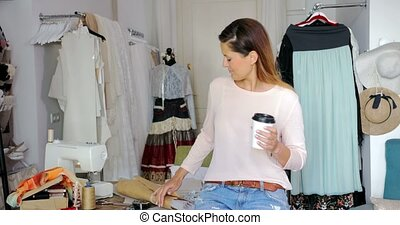 Smiling female tailor with coffee - Young woman sitting on...