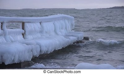 Ice covered pier by the stormy Baltic Sea in Helsinki,...