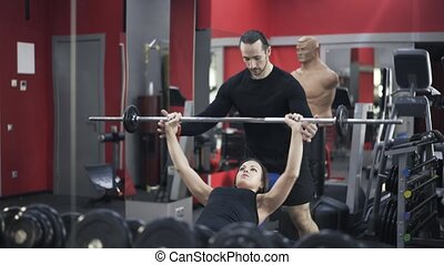 Coach helping woman to lift barbell - Young bearded coach is...