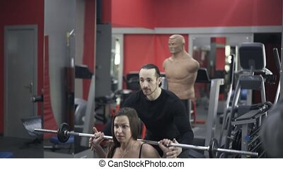 Coach helping woman to lift barbell in a gym - Young bearded...