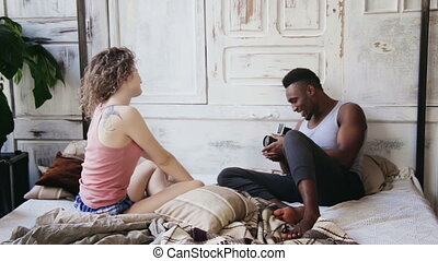 Photoshoot on pajamas in morning. Multiracial couple on the...