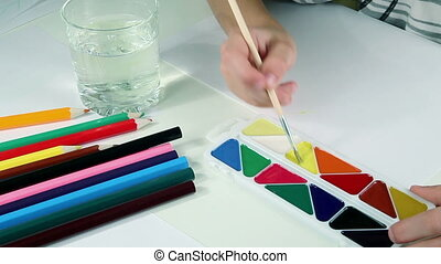 Little Boy Draws Paints - Little boy draws a yellow sun with...
