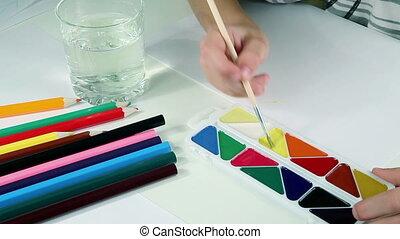 Little Boy Draws Paints - Little boy draws a yellow sun with...
