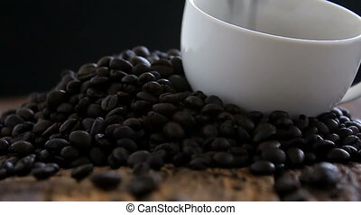 Close up shot of dark roasted coffee beans fall into white...