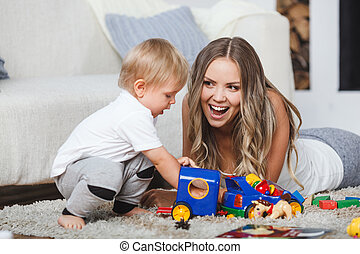 cute mother and child boy play together indoors at home