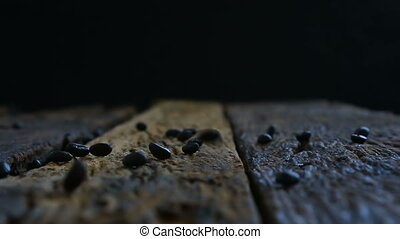 Roasted coffee beans fall into the wooden floor with dark...