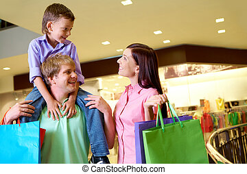 Shoppers - Portrait of joyful woman looking at her son on...